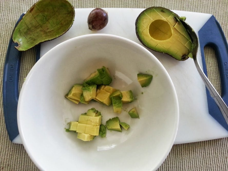 White bowl with diced avocado.