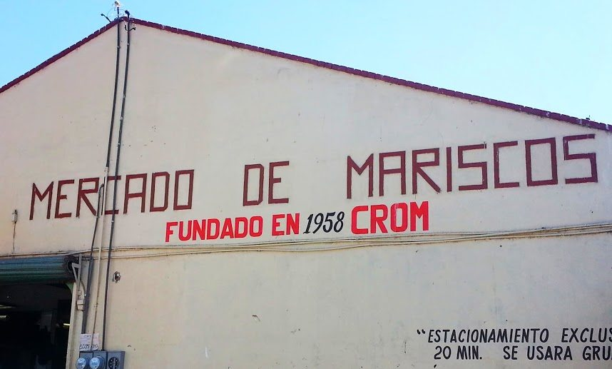 "The building for the fish market in Ensenada with a sign that reads ""Mercado de Mariscos."""