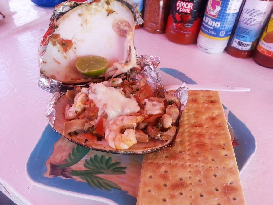 Almejas gratinadas (Clams with melted cheese) opened and served next to saltine crackers.
