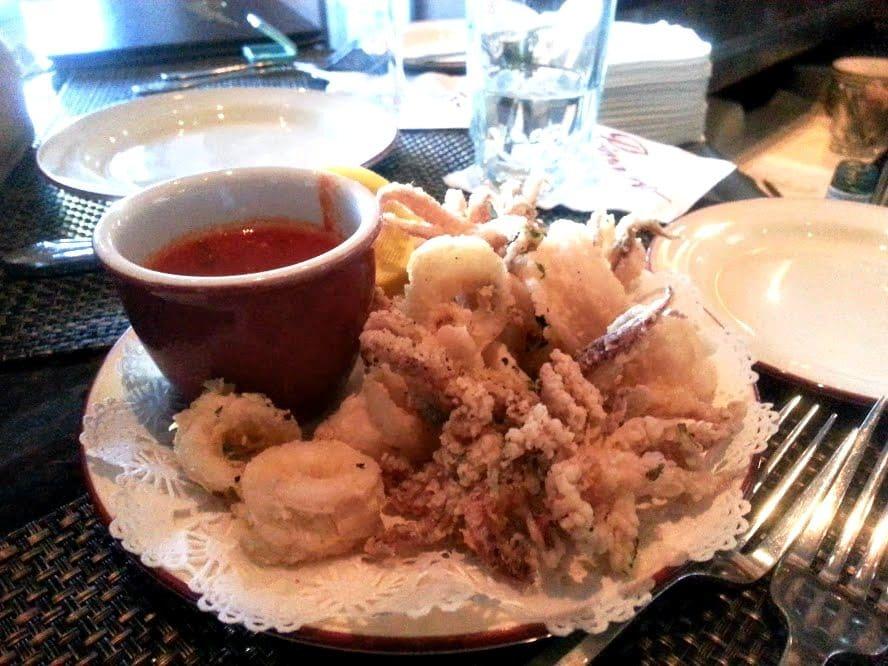 Calamari fritti next to dipping sauce on a white plate at Primavera Restaurant.