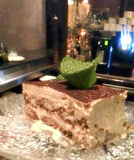 Tiramisu topped with mint leaves at a restaurant.