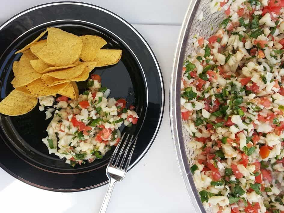 Fishless ceviche on a black plate and served with chips.
