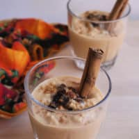 Pumpkin Arroz con Leche served in a glass cup topped with raisins and a cinnamon stick to the side.