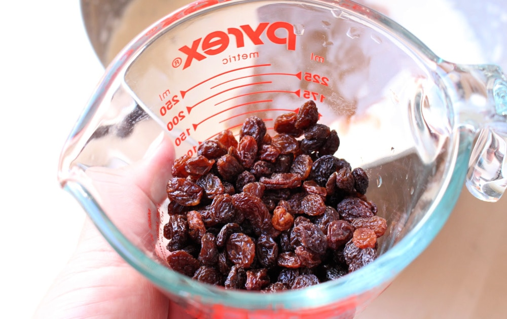 Hand holding a measuring cup with raisins inside.