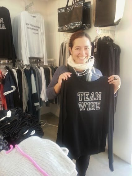 Maggie holding a team wine t-shirt at Kipston
