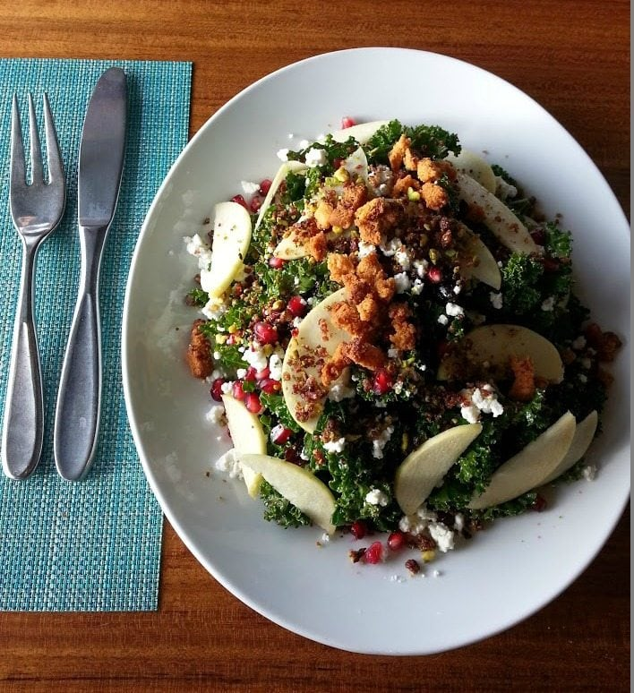 Kale Salad with apples, cranberries and goat cheese served on a white plate next to one fork and knife