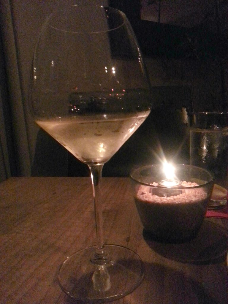 Glass of wine next to a candle