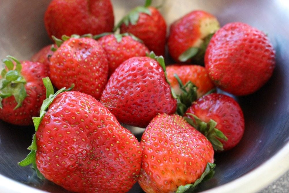 Fresh strawberries in a metal bowl