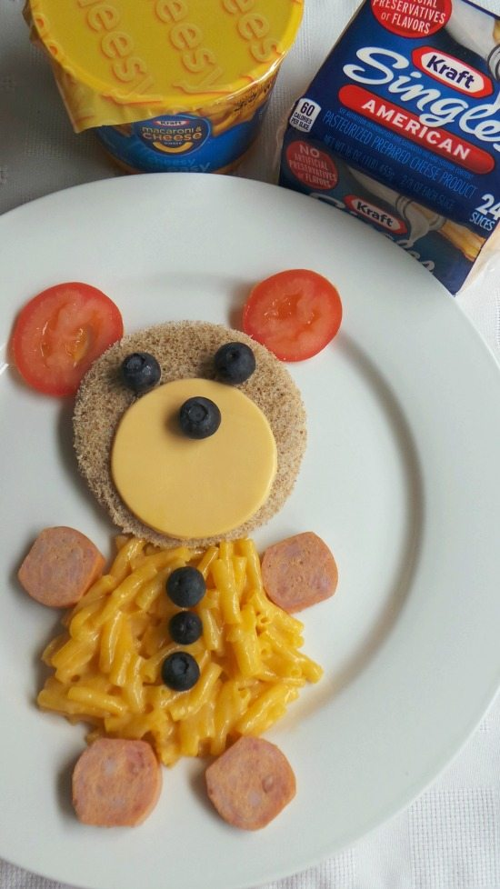 A bear made with cheese, mac and cheese, sausages, tomatos and blueberries