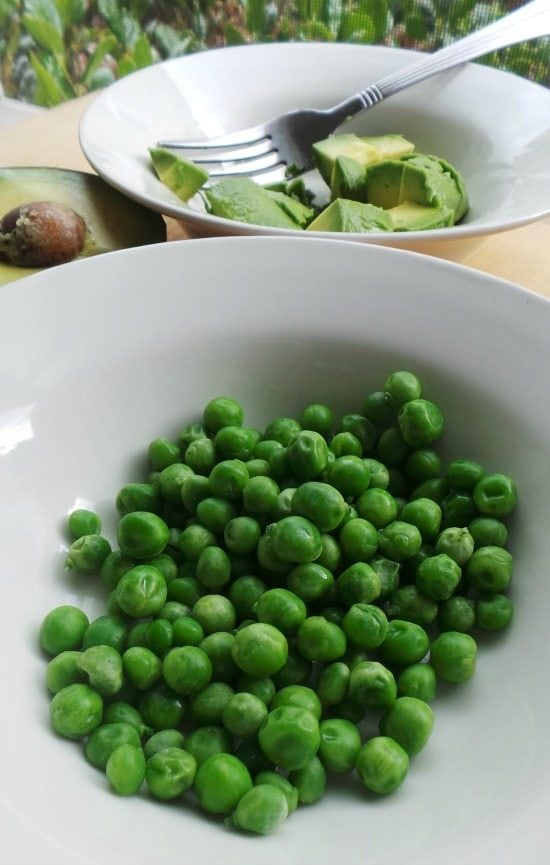 Peas in a plate next to another plate with avocado and a fork