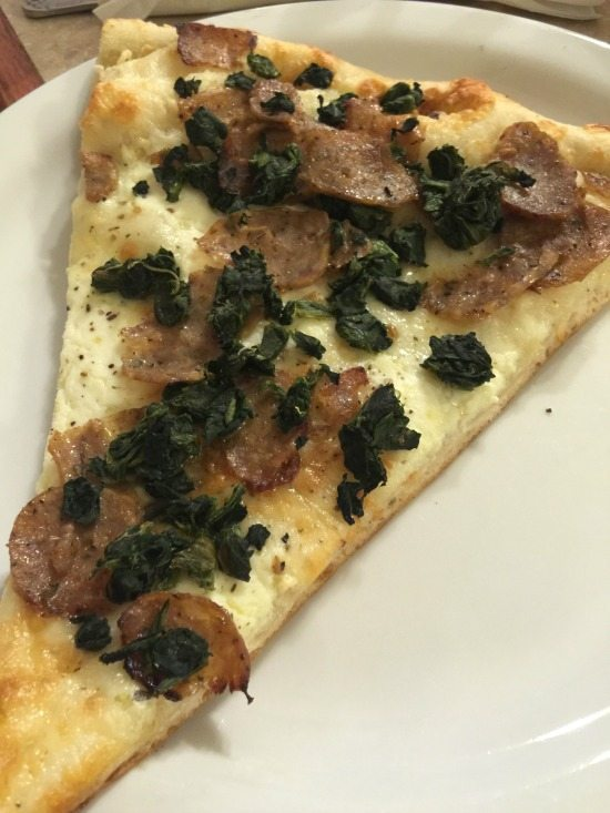 Pizza Slice with sausage and spinach at Casanova Brothers