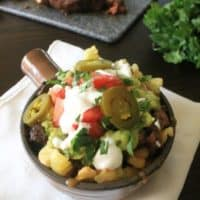 Carne Asada Fries in a container with white napkin slices of beef.