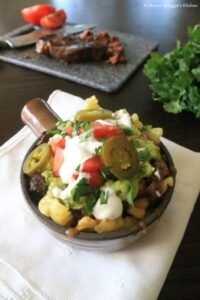 Carne Asada Fries in a container with white napkin slices of beef