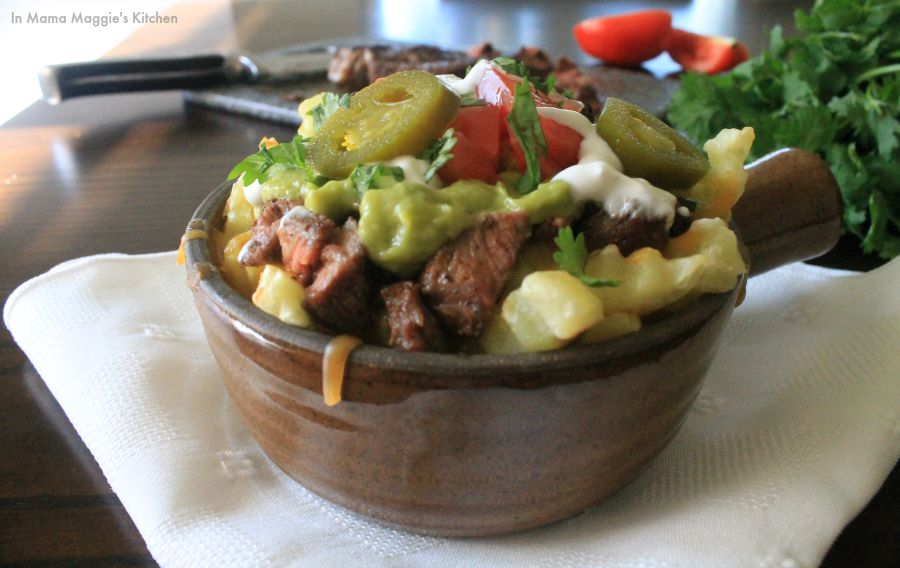 Carne asada fries in a bowl topped with all the fixings.