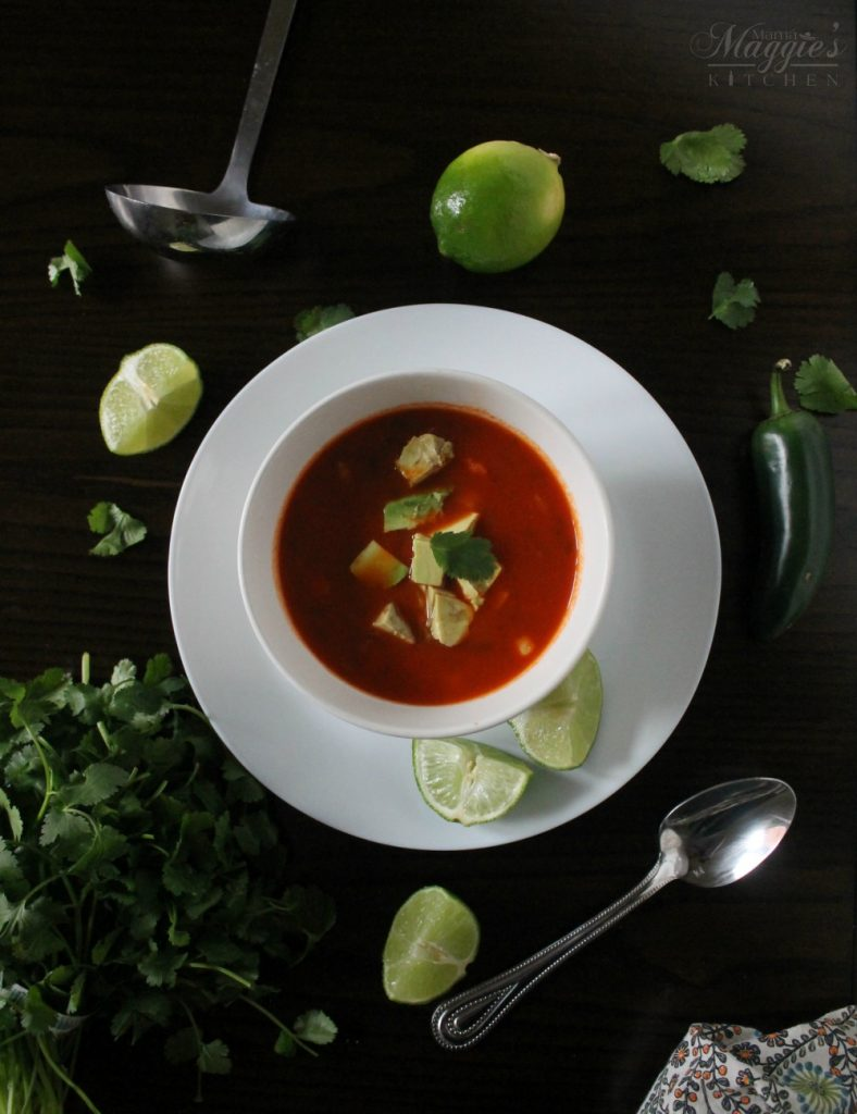 Caldo de Camarón, or Mexican Shrimp Soup in a while bowl topped with diced avocado and surrounded by lime wedges, cilantro, jalapeno, spoon, and ladle on a dark brown table