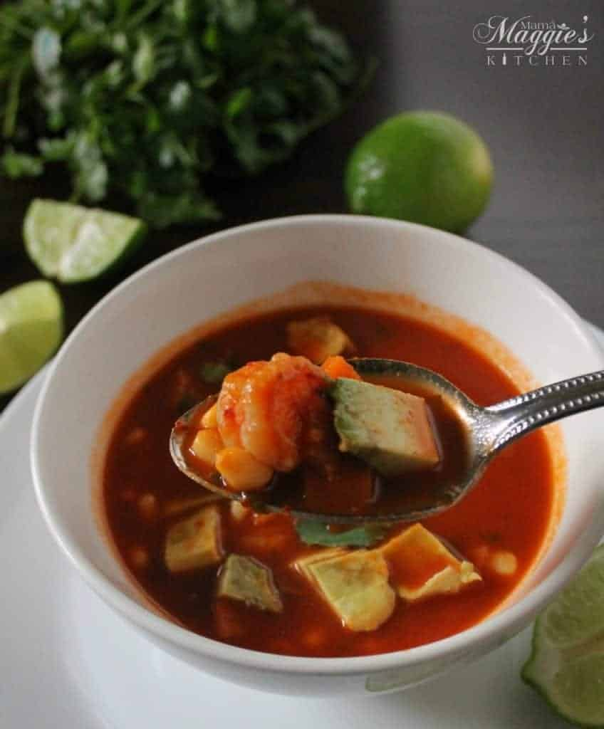 Caldo de Camarón, or Mexican Shrimp Soup in a white bowl with a rich, guajillo sauce. Spoon lifting shrimp and avocado. Cilantro and lime on a dark brown table.