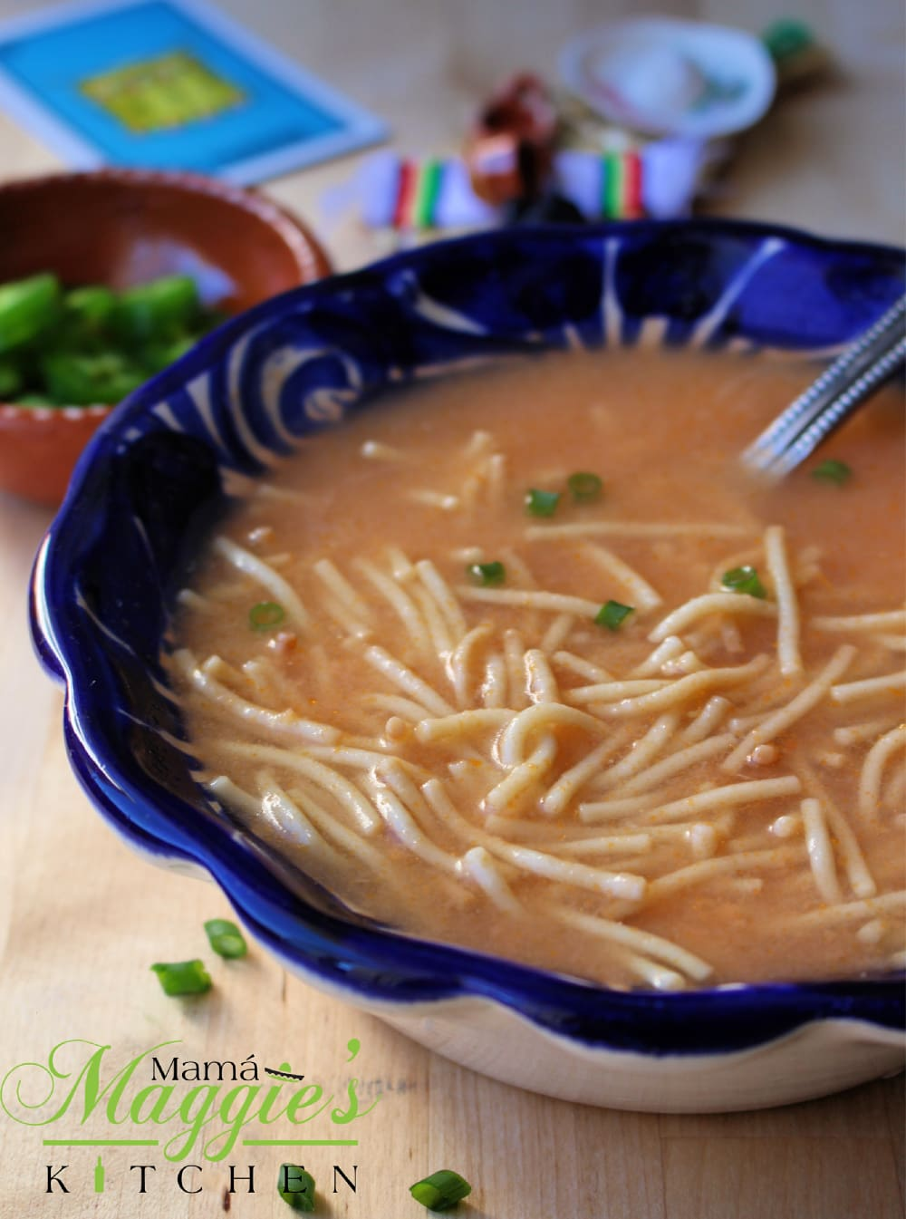 A blue bowl with Sopa de Fideo (Mexican Noodle Soup) surrounded by decorative clay plate.