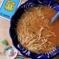 A blue bowl with Sopa de Fideo (Mexican Noodle Soup) surrounded by decorative Mexican toys.