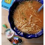 Sopa de Fideo in a blue bowl surrounded by decorative Mexican artisan pieces.