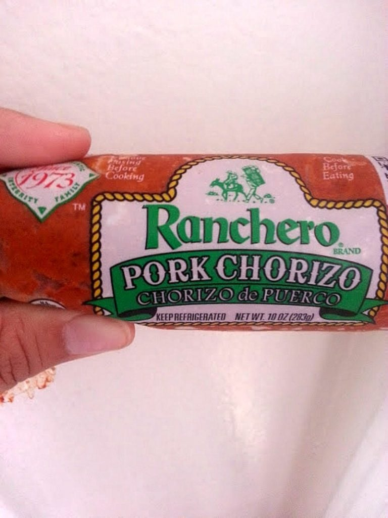 Hand holding a package of pork chorizo.