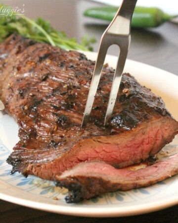 A fork inserted in the center of a grilled tri tip with a slice cut off from the meat.