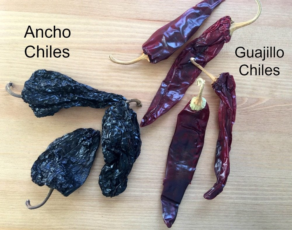 Dried ancho chiles next to dried guajillo chiles on a wooden table.