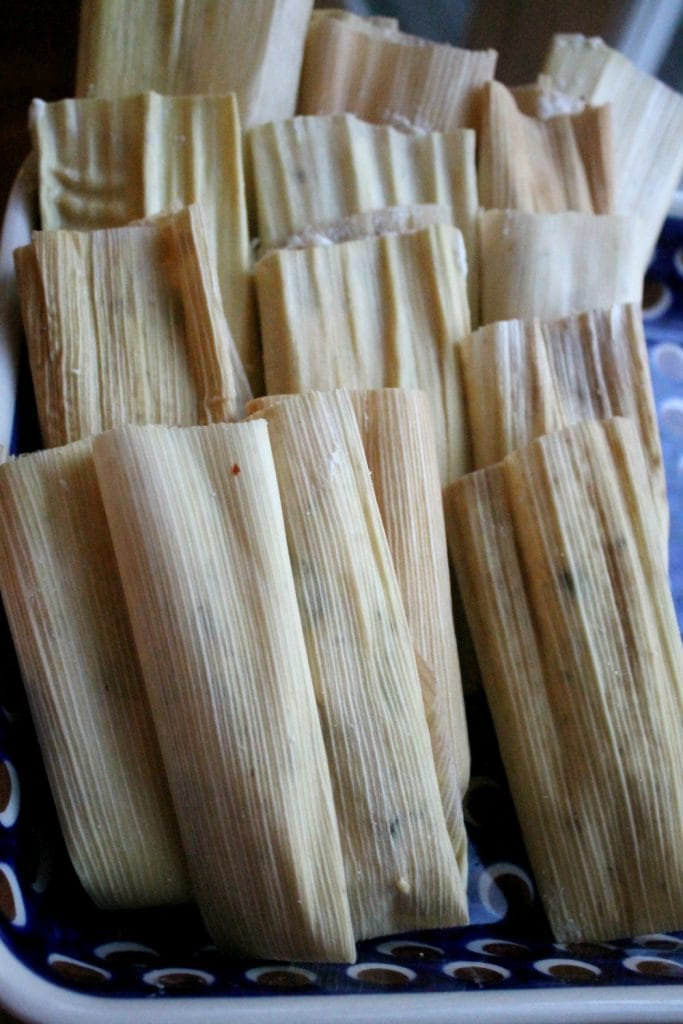 Tamales standing upright on a platter.