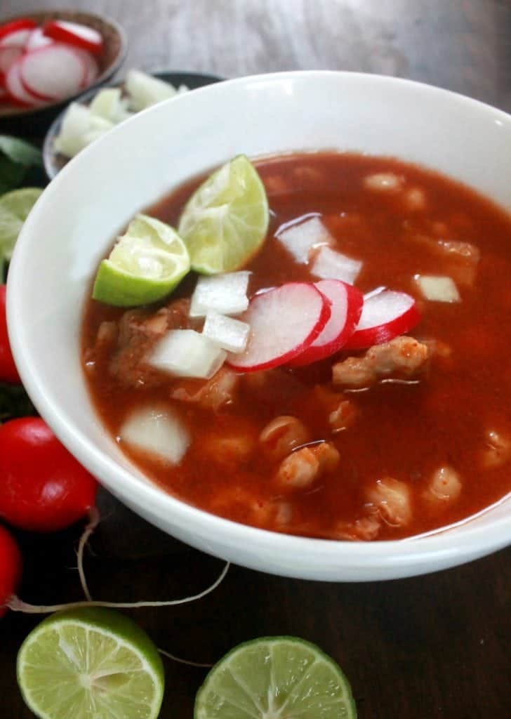 Pozole Rojo in a white bowl and topped with lime and radish slices.
