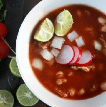 Pozole Rojo in a white bowl topped with radishes and lime.