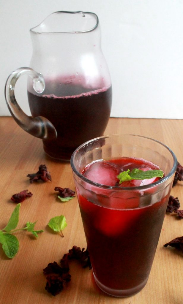 Agua de Jamaica served in a cup and in a pitcher surrounded by dried hibiscus leaves.