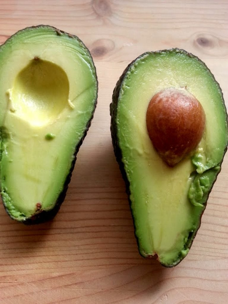 Ripe avocado cut in half. One avocado with a pit. The other pit has been removed.