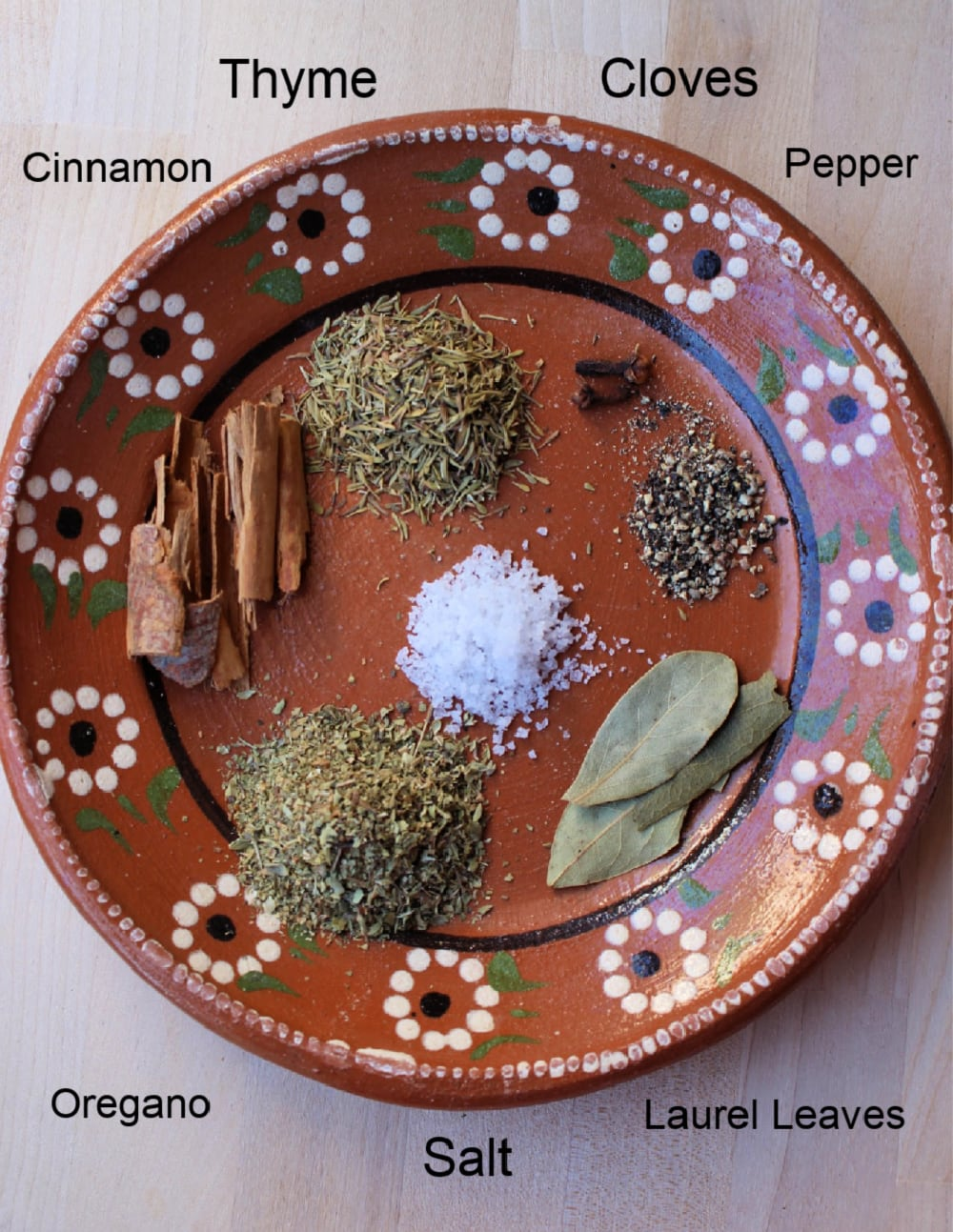 Spices to make the Birria de Res sauce on a decorative Mexican clay plate.
