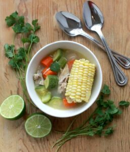 Caldo de Pollo, or Mexican Chicken Soup served in a white bowl and surrounded by lime and spoons.