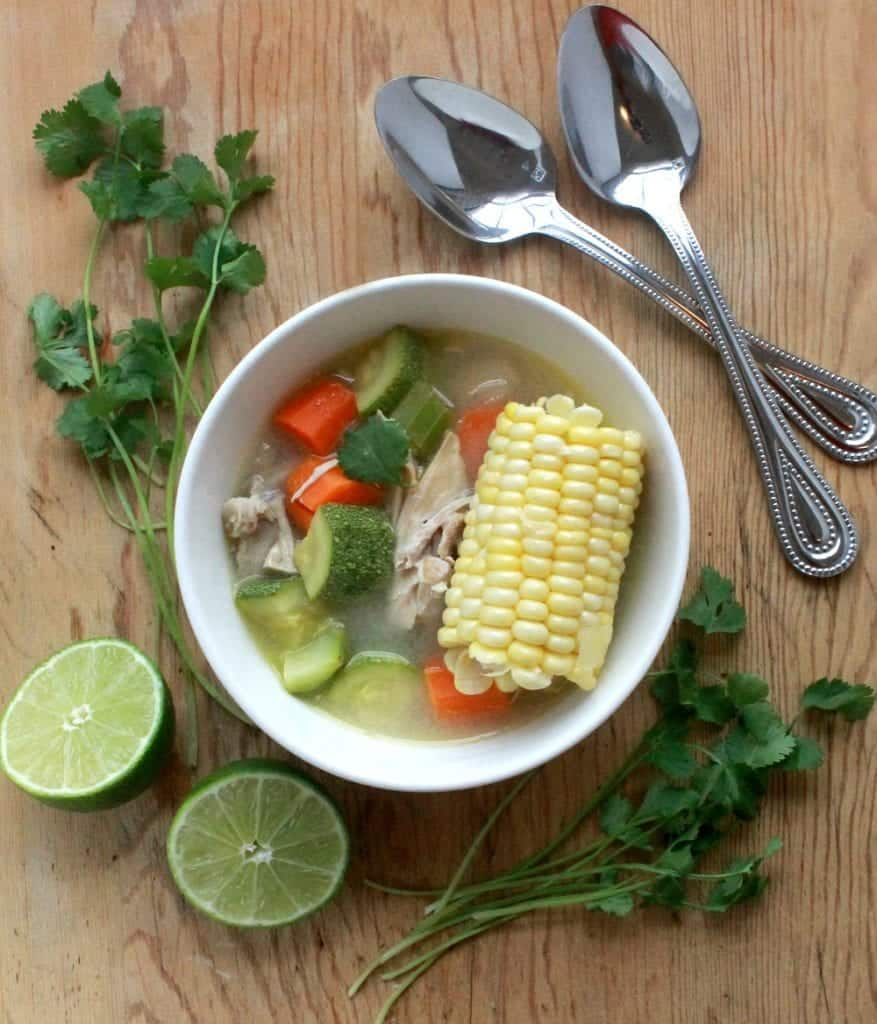 Caldo de Pollo, or Mexican Chicken Soup, served in a white bowl and surrounded by spoons, cilantro, and lime wedges.