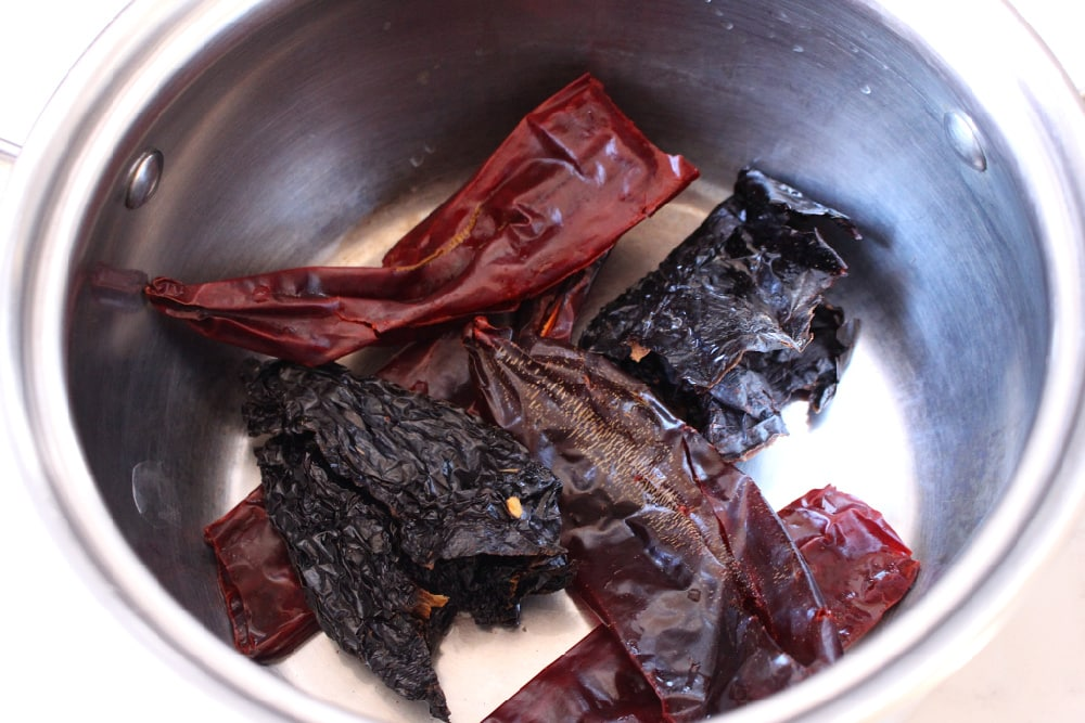 Dried chiles in a stainless steel pot.