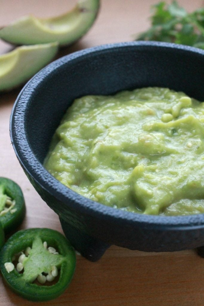 Salsa de Aguacate, or Avocado Salsa, in a black bowl surrounded by jalapeno slices and avocado wedges.