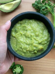 Hand holding a black bowl of Salsa de Aguacate, or Avocado Salsa