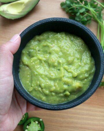Hand holding a black bowl of Salsa de Aguacate, or Avocado Salsa