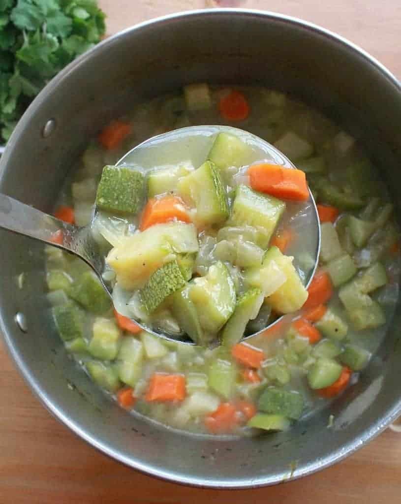 A ladle with Caldo de Verduras over a pot of Mexican Vegetable Soup.