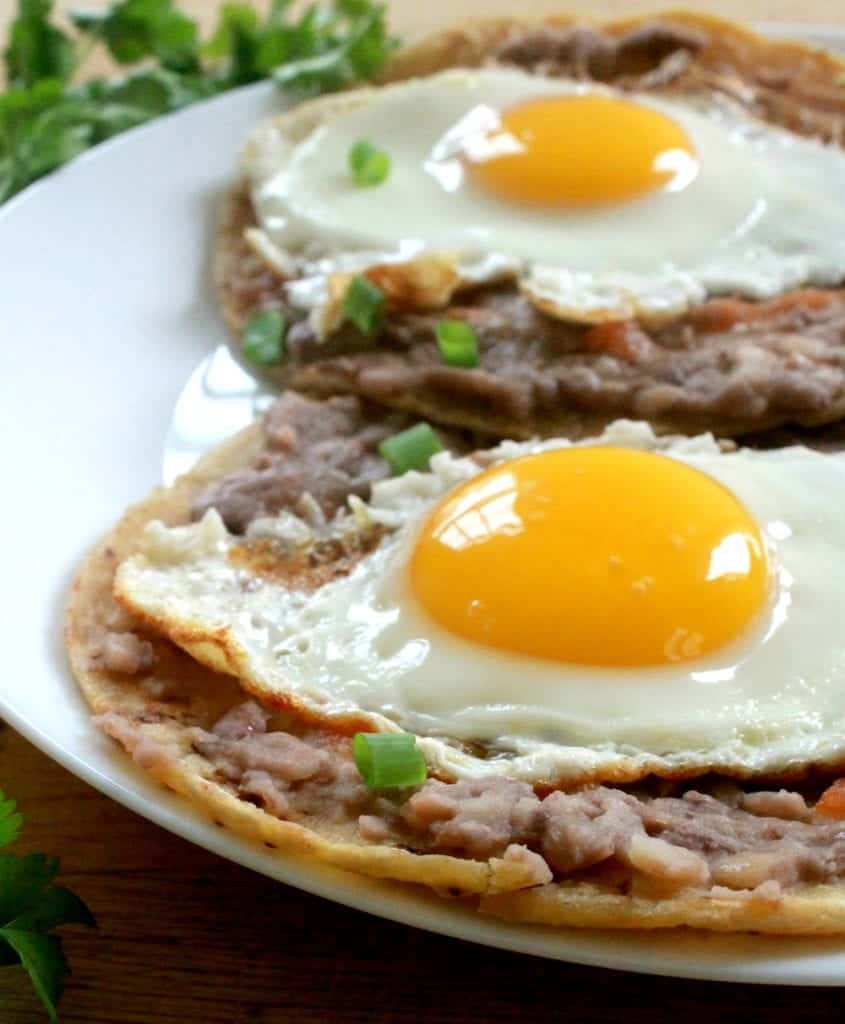 Huevos Rancheros on a plate topped with a rummy yolk and sitting on a bed of refried beans.