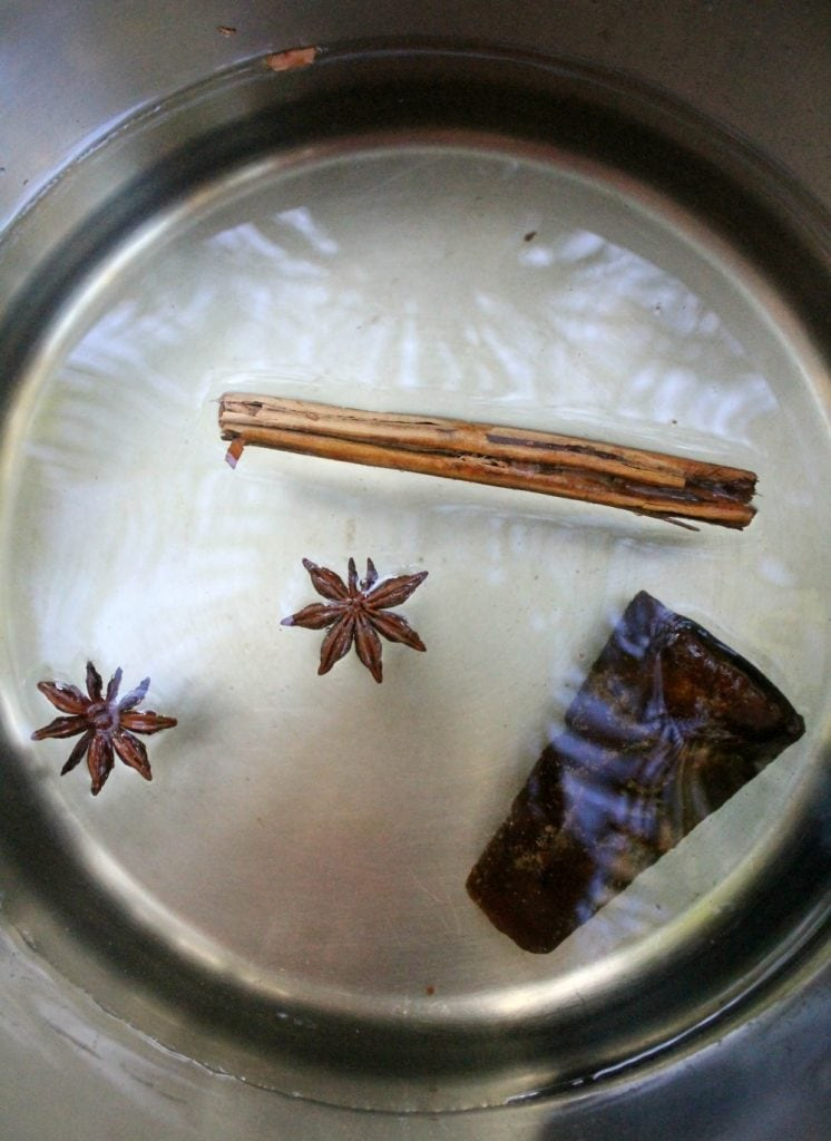 A picture of a sauce pan with piloncillo, star anise, and cinnamon all swimming in water.