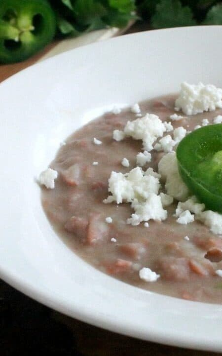 Refried beans topped with slice of jalapeno and crumbled queso fresco.