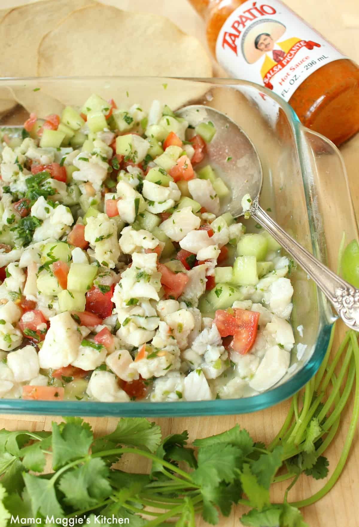 Fish ceviche in a glass baking dish with a sliver spoon and surrounded by cilantro.
