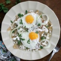 Green Chilaquiles served on a plate and topped with two runny eggs.