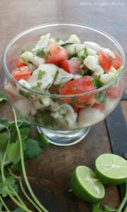 Fish Ceviche in a glass bowl surrounded by lime and cilantro stems.
