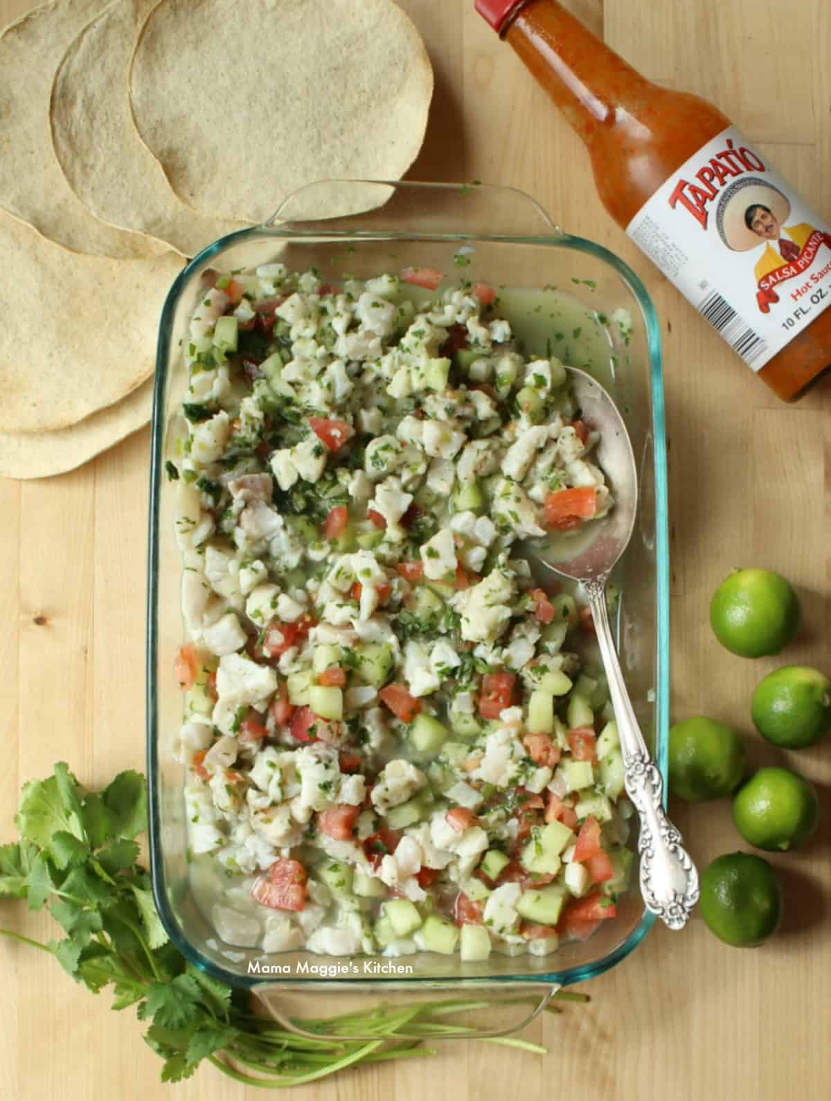 Fish ceviche in a baking dish surrounded by lime, cilantro, hot sauce, and tostadas.