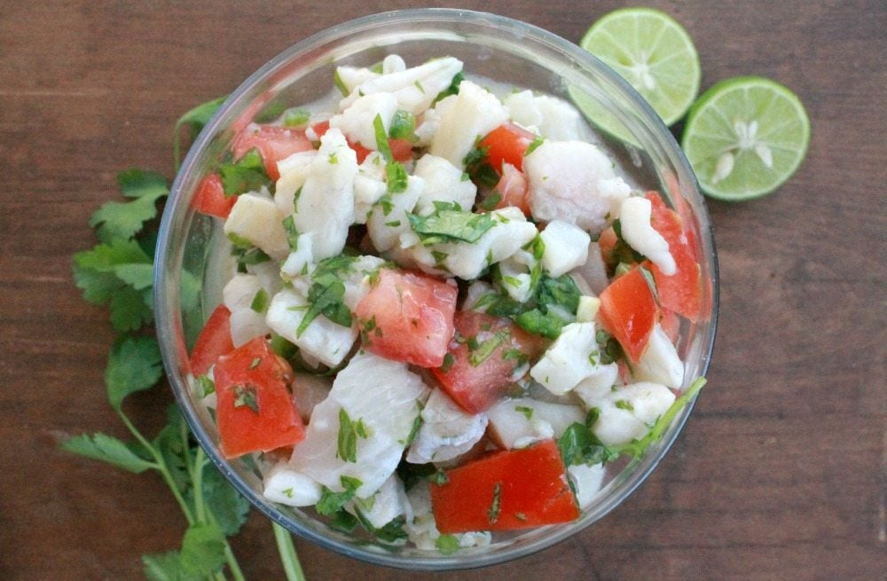 Fish Ceviche (Ceviche de Pescado) in a glass bowl on a wooden surface and surrounded by cilantro.