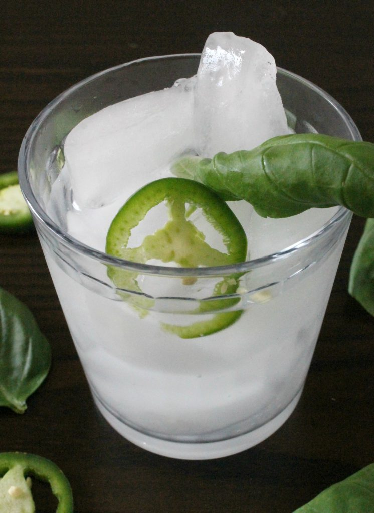 Jalapeño Basil Margarita in a glass with ice, jalapeno slices, and basil leaves.