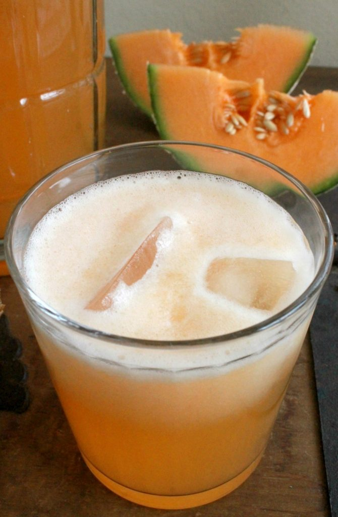 Cantaloupe Agua Fresca in a glass topped with ice surrounded by cantaloupe slices.