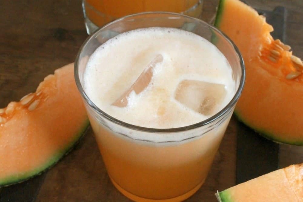 Cantaloupe Agua Fresca in a glass topped with ice cubes and surrounded by cantaloupe wedges.